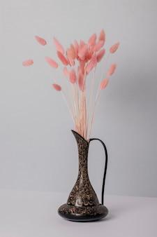 Droge bloemen in een vaas op een grijze muur.