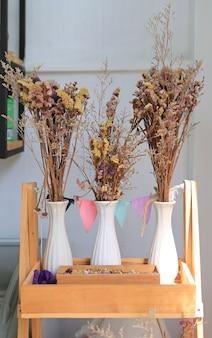 Droge bloemen in vaasdecoratie op houten plank bij koffie.