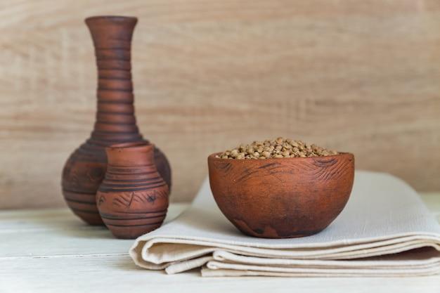 Droge boekweit in bruine kleikom op houten lijst. glutenvrij graan voor een gezond dieet