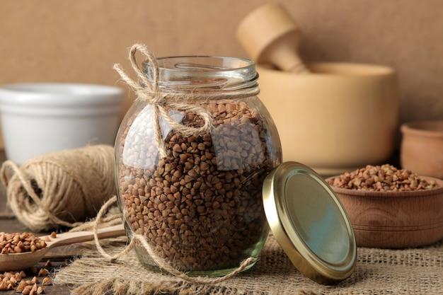Droge boekweitgrutten in een glazen pot op de voorgrond op een houten bruine tafel. granen. gezond eten. pap.