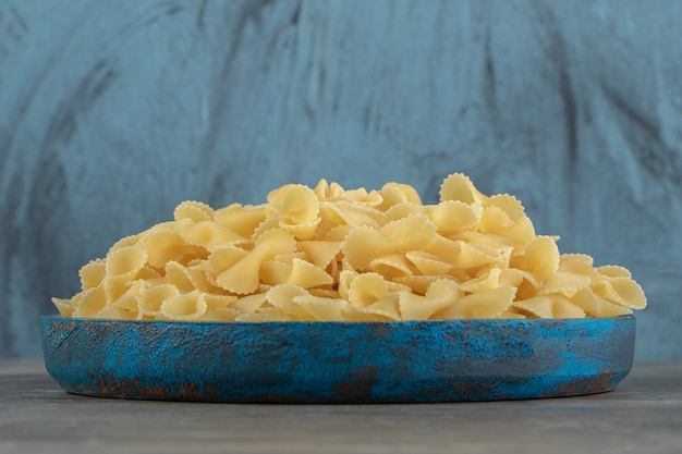 Droge boog pasta op blauw bord