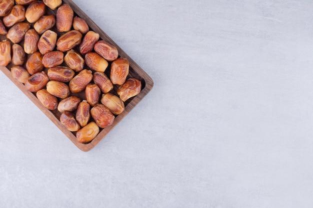 Droge bruine dadels in een houten bord. hoge kwaliteit foto