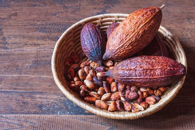 Droge cacaopeulen en cacaobonen in mand op houten achtergrond