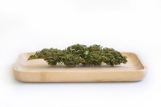 Droge cbd-plantknoppen op een houten bakje met een witte achtergrond