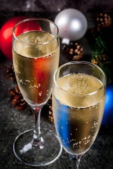 Droge champagne in glazen, kerstmis kleurrijke ballen, denneappels, de samenstelling van het nieuwjaarstilleven op donkere steen, selectieve nadruk copyspace