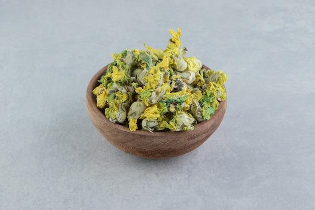 Droge chrysantenbloemen in houten kom.
