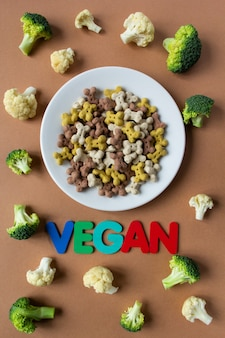 Droge crunchies van de hond in de vorm van bot op een witte plaat. bloemkool en broccoli op beige achtergrond. veganistisch concept met letters.
