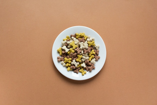 Droge crunchies van de hond in vorm van been op witte plaat op beige achtergrond. kopieer ruimte en plat.