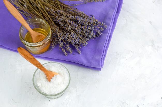 Droge de lavendelbloemen van het hoogste uitzicht, honingskruik, overzees zout, kuuroord dat op witte sjofele concrete achtergrond wordt geplaatst