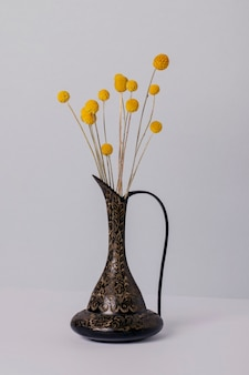 Droge decoratieve plant in een vaas op een grijze muur.