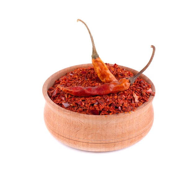 Droge en gemalen chili peper vlokken geïsoleerd op een witte achtergrond. rode chili peper in de houten kom.