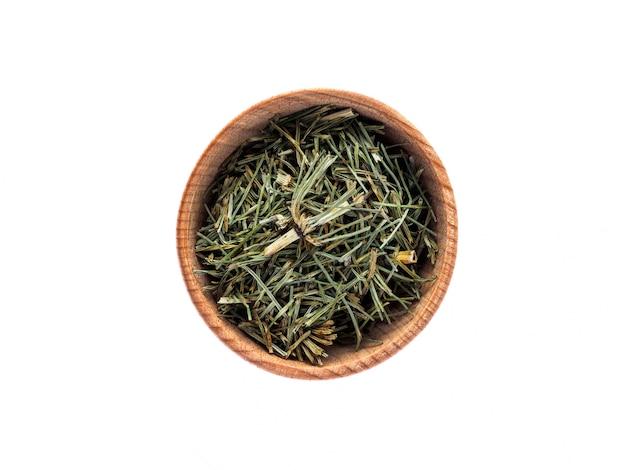 Droge equisetum arvense of paardestaart in een houten kop op een witte tafel