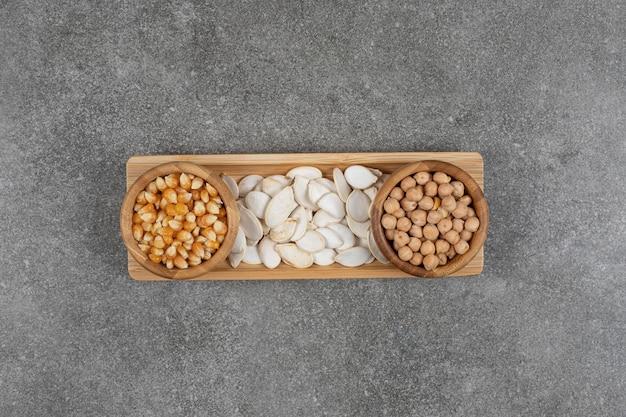 Droge erwten, pompoenpitten en maïskorrels in houten kommen.