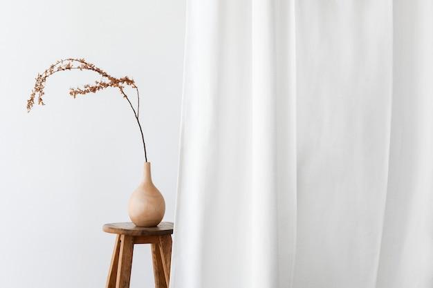 Droge forsythia-tak in een houten vaas op een krukje bij een wit gordijn
