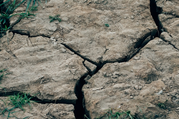Droge gebarsten de textuurachtergrond van de aardegrond.