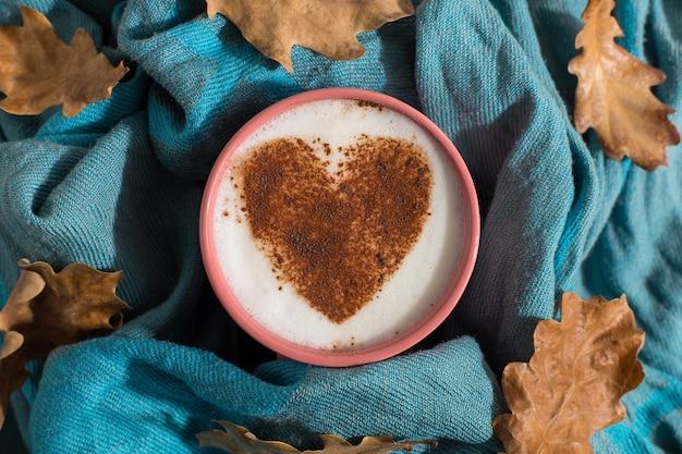 Droge gele bladeren, een blauwe sjaal, koffie met een hartpatroon op tafel, een goede morgen is de beste startdag. herfst stemming achtergrond, copyspace.