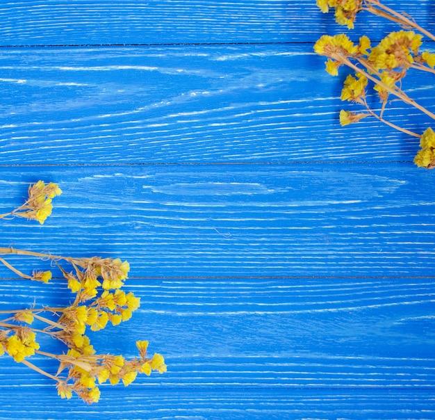 Droge gele bloemen die een kader op een heldere blauwe houten achtergrond vormen