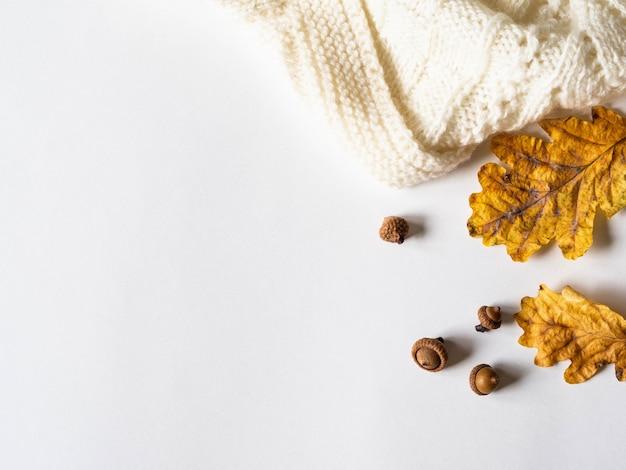 Droge gele eikenbladeren en eikels en warme gebreide lichte plaid. de herfstsamenstelling op een witte achtergrond