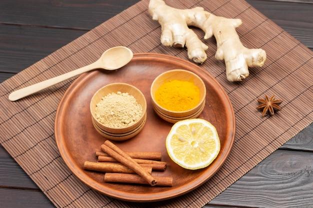Droge gember en kurkumapoeder in houten kommen, schijfje citroen op keramische plaat. gemberwortel op tafel. houten achtergrond. bovenaanzicht