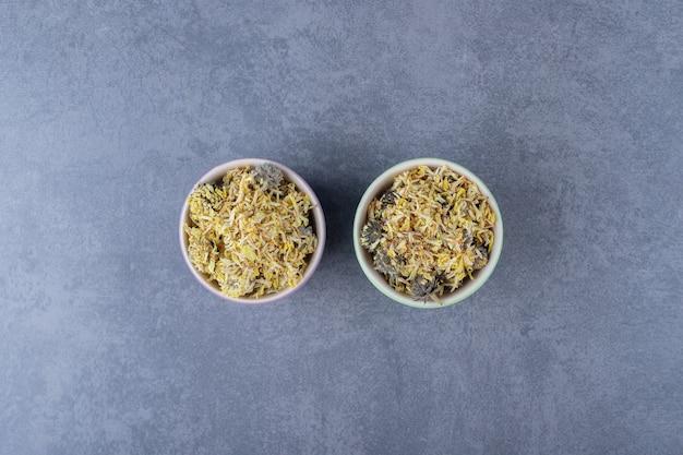Droge gezonde bladeren in kom. twee kleine kommen vol met kom op grijze achtergrond.