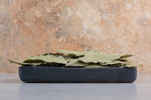 Droge groene laurierblaadjes geïsoleerd op betonnen achtergrond.