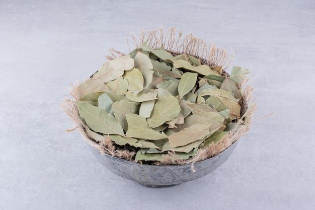 Droge groene laurierblaadjes in een rustieke beker. hoge kwaliteit foto