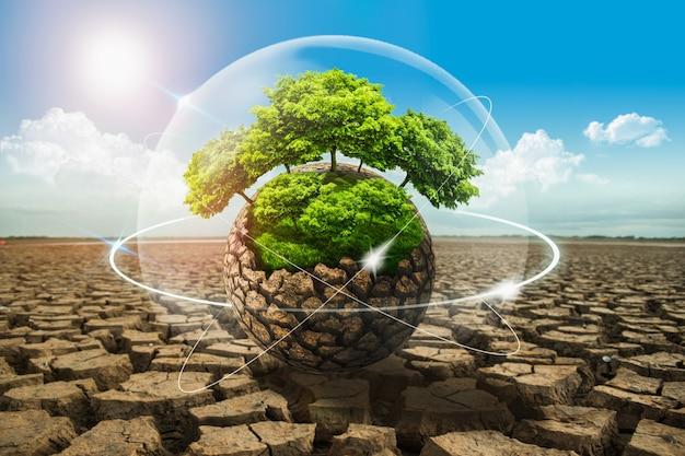 Droge grond veroorzaakt door droogte met bomen in een dom beschermde de aarde tegen milieurampen