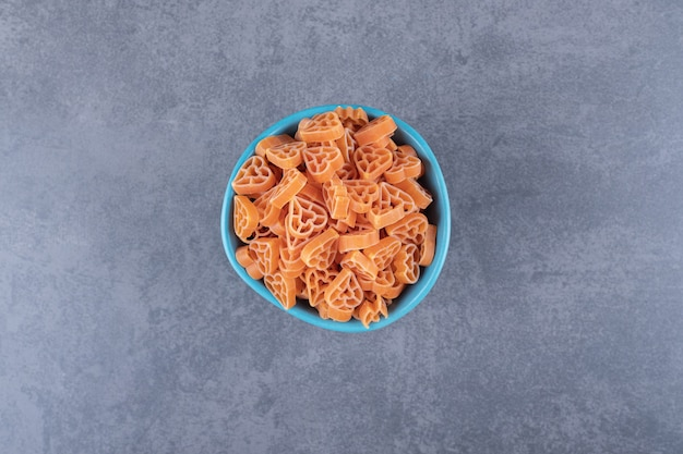Droge hartvormige pasta in blauwe kom.