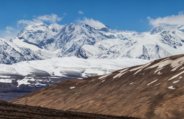 Droge hellingen en met sneeuw bedekte toppen van het pamir-gebergte in tadzjikistan