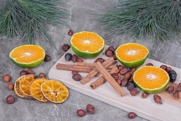 Droge heupen en stukjes sinaasappel met verse sinaasappelen op een houten bord.