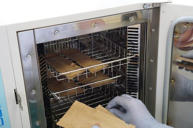 Droge hitte voor sterilisatie-instrumenten in een schoonheidssalon. handen van meester