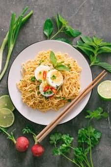 Droge instant noedels zetten ei met verse kruiden, garnituur van koriander en aziatische basilicum, citroen, limoen op donkere stenen achtergrond