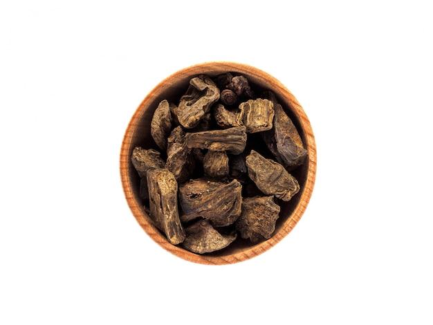 Droge inulawortel in houten kop op witte lijst