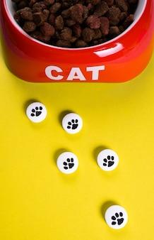 Droge kattenbrokjes in een rode kom en witte pillen met foto van poot