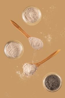 Droge klei voor gezichtsmasker in glazen kom en houten lepels op neutrale beige achtergrond zelfzorgconcept