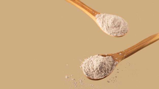Droge klei voor gezichtsmasker in houten lepels op neutrale beige achtergrond zelfzorgconcept kopieer de ruimte