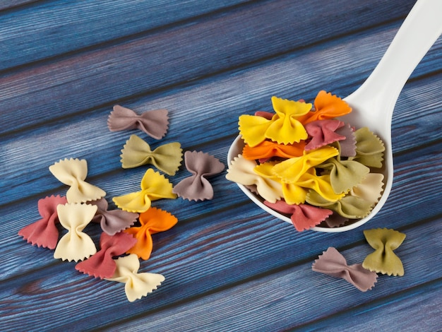 Droge kleurrijke italiaanse deegwaren farfalle of bogen met lepel op donkerblauwe houten achtergrond. met kopie ruimte