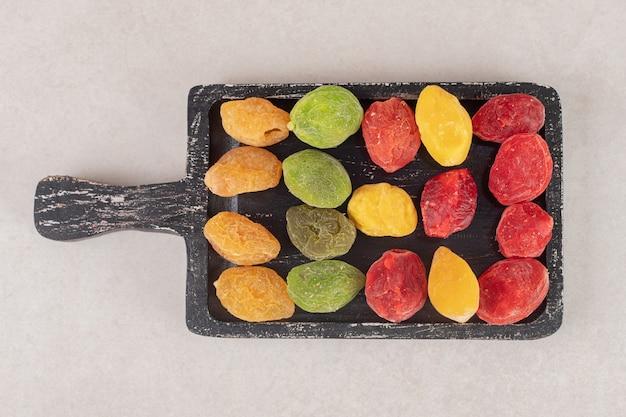 Droge kleurrijke kersen op een houten schotel.