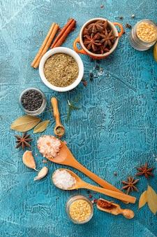 Droge kleurrijke kruiden en specerijen anijs, paprika, saffraan, peper, zout, laurier, kaneel in kleine kommen op blauw