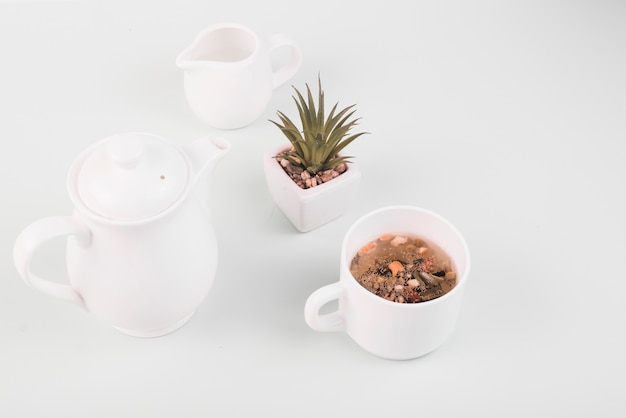 Droge kruiden in de thee dichtbij aardewerk op witte achtergrond
