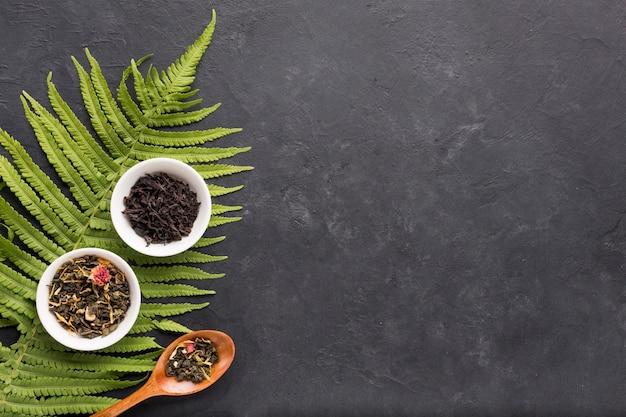 Droge kruidenthee in witte ceramische kom met varenbladeren op zwarte achtergrond