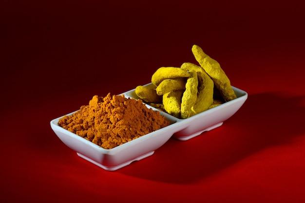 Droge kurkumapoeder en wortels of blaft in witte plaat