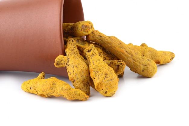 Droge kurkumawortels of blaft in geïsoleerde kleipot