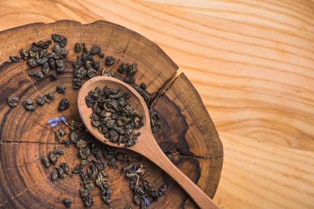 Droge lavendelbloemen op lepel over de houten boomstomp