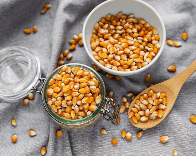 Droge maïszaden in pot en kom op grijze textielachtergrond
