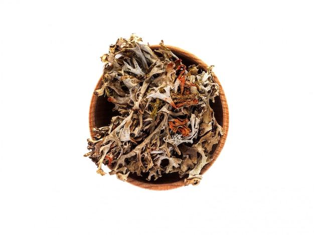 Droge mossen of bryophyta in een houten kop op een witte tafel