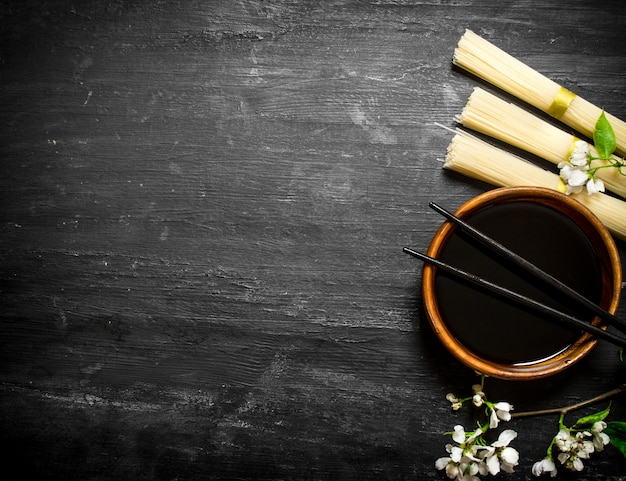 Droge noedels met sojasaus en de kersentakken op een zwarte houten achtergrond