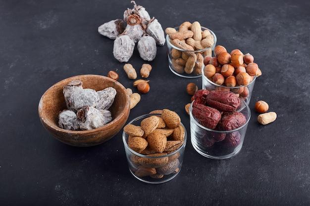 Droge noten en fruit in een glas en houten kopjes op grijze achtergrond.