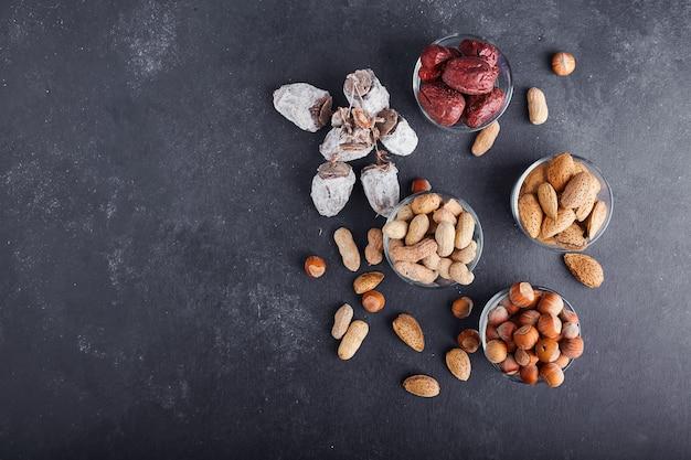 Droge noten en fruit in een glas en houten kopjes op grijze ondergrond, bovenaanzicht.
