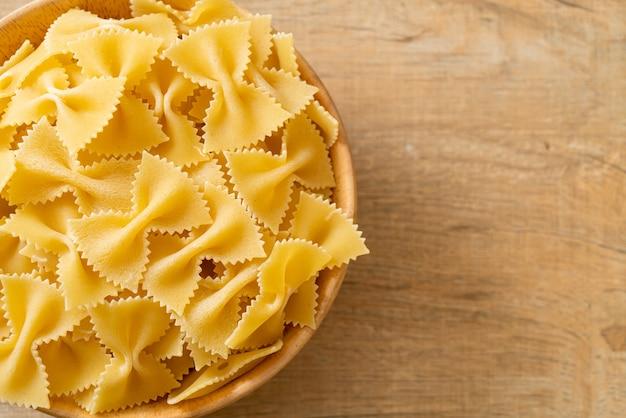 Droge ongekookte farfalle pasta in houten kom